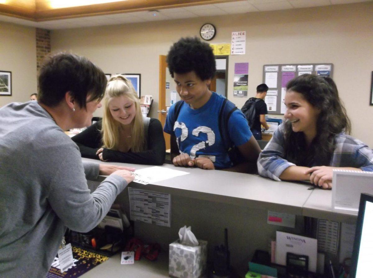 Students Savannah Drake-Felton, Carlin Braenne and Izzy Molgaard get help from Career Center employee Jill Nemeth. (SPASH Highlights photo)